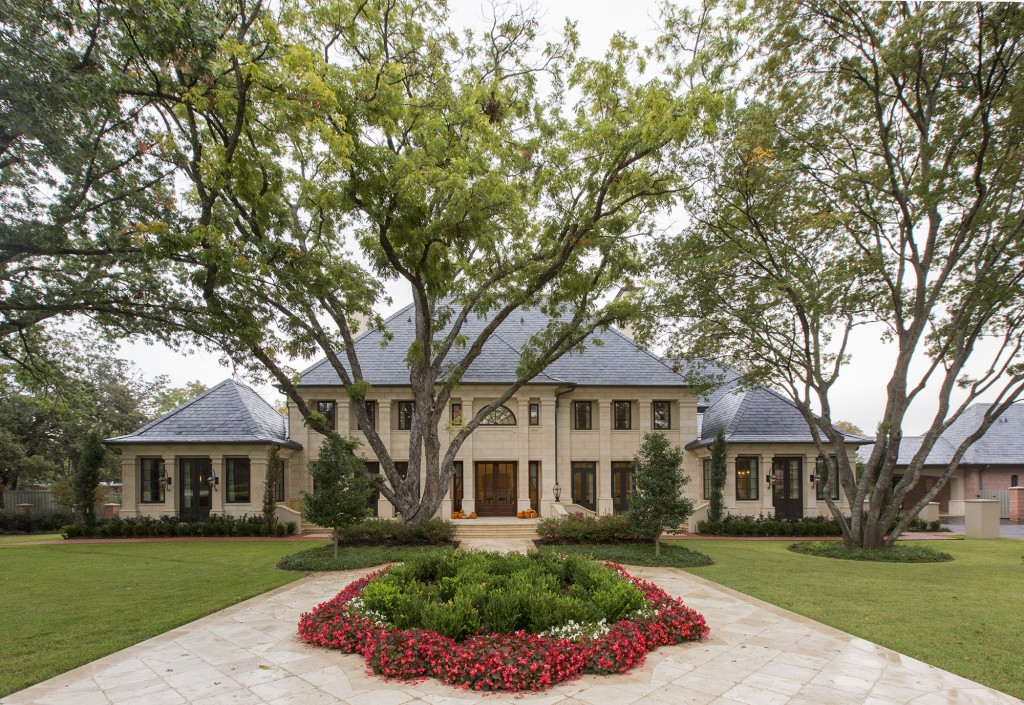 This french style home is right at home on this beautiful tree-filled lot.